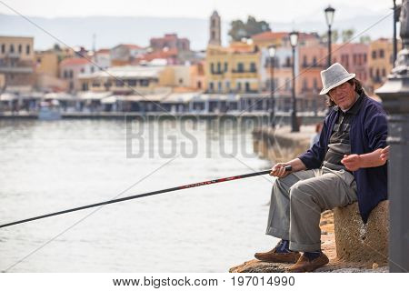 CHANIA, GREECE - APRIL 3, 2017 : Angler at the harbour of Chania on Crete, Greece. Chania is the second largest city of Crete and the capital of the Chania regional unit.