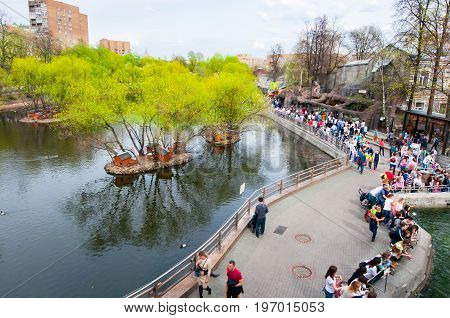 Moscow Russia-May 01: Moscow Zoo during the midday crowd of people go sightseeing on May 01 2017 in Moscow. There are two large territories in the zoo with a high bridge between them.