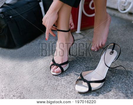 Barefoot woman's tired legs closeup. Modern social behavior, confident and uninhibited girl taking off her shoes poster
