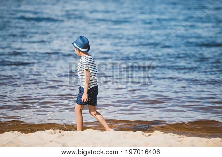 side view of little boy in casual clothing walking on sandy beach alone