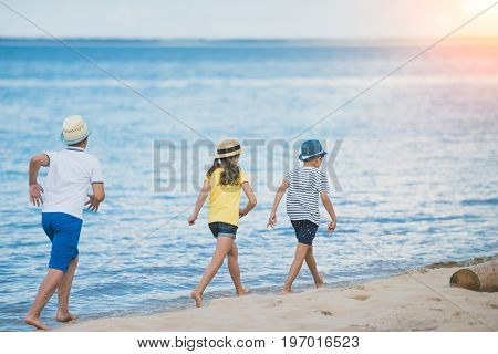 Back View Of Kids In Casual Clothing Walking On Beach Together