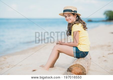 Side View Of Cute Little Girl Sitting On Wooden Trunk On Sandy Beach