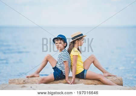 Side View Of Kids Holding Hands While Sitting On Wooden Trunk On Sandy Beach