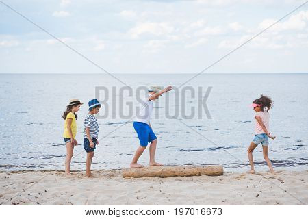 Side View Of Multicultural Children Playing On Sandy Beach