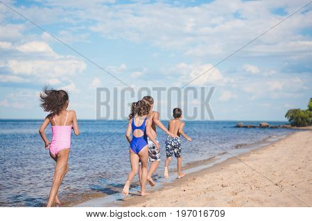 Back View Of Children In Swimsuits Running On Sandy Beach