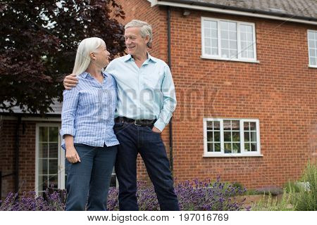 Portrait Of Retired Couple Standing Outside Home