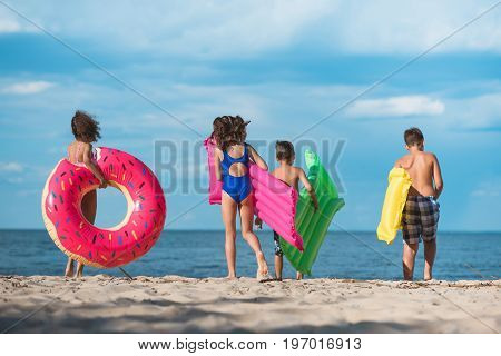 Back View Of Group Of Kids With Inflatable Mattresses Walking On Beach