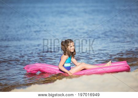 Side View Of Little Girl Resting On Inflatable Mattress At Seaside