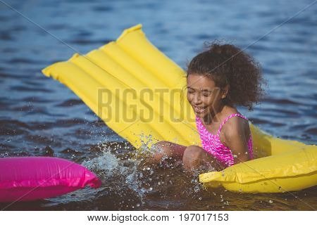 Portrait Of Laughing African American Girl Having Fun On Inflatable Mattress