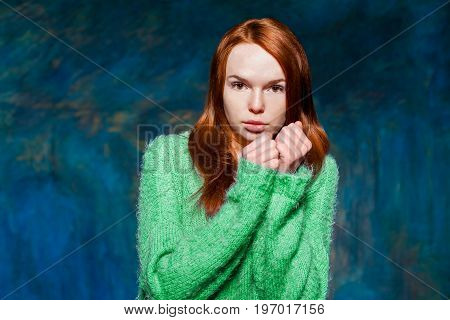 young pretty cold redhead girl in greem pullover over dark blue background. beauty model woman with luxurious red hair. hairstyle. holiday makeup