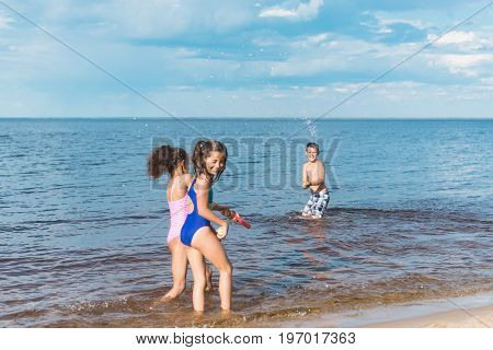 little children with water toys playing together at seaside