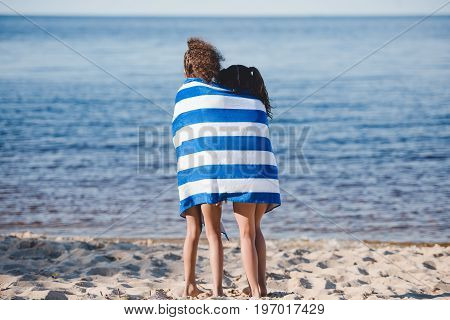 Back View Of Little Girls In Colorful Striped Towel Standing On Beach