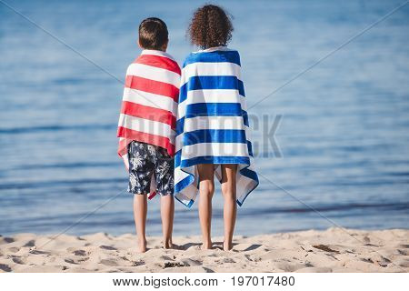 Back View Of Boy And Girl In Towels Standing Together On Seashore