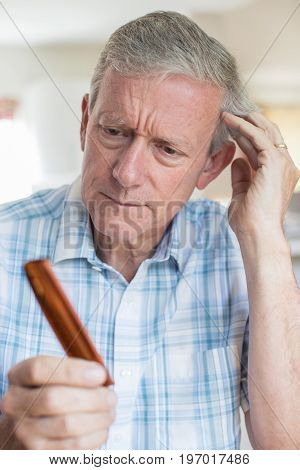 Senior Man With Comb Concerned About Hair Loss