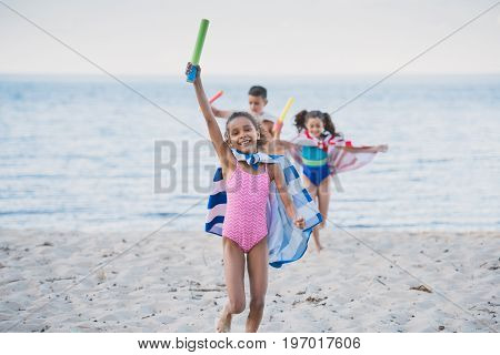 Multicultural Kids In Towels With Water Toys In Hands Running On Beach