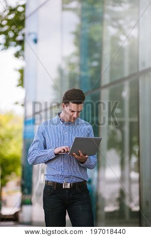 Workaholic freelancer working on street. Attentive businessman with laptop