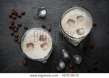 Coffee liqueur in glasses with ice and coffee beans top view on black.
