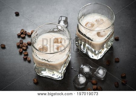Coffee liqueur in glasses with ice and coffee beans on black table.
