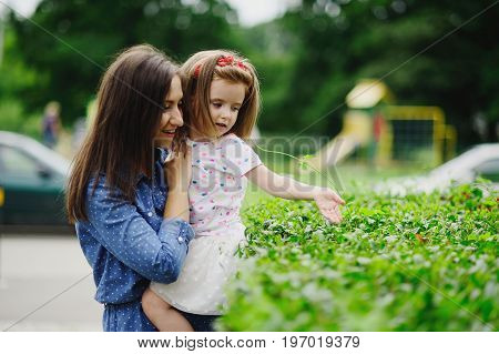 Young mother walks in the park with the little daughter. The woman holds the baby on hands. She gently presses to herself the daughter. The woman holds the baby on hands. She gently presses to herself the daughter.