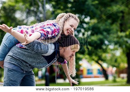 Young extraordinary couple fool around in the summer park. The guy carries girlfriend on his back.