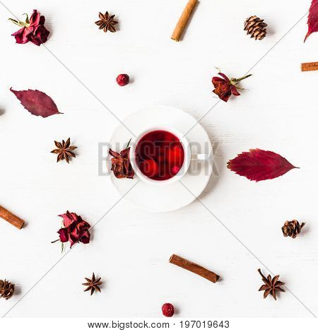 autumn composition cup of fruit tea with autumn leaves cinnamon sticks star anise cones dried rose flowers top view flat lay