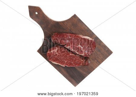 two fresh raw marble beef meat sirloin porterhouse steak on dark wood cut board isolated on white background