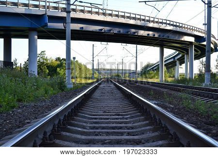 Railroad tracks pass under the road overpass.