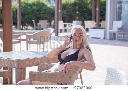 girl at the beach restaurant talking on the phone