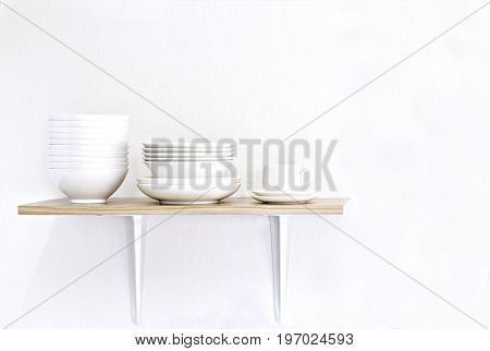Stack of white bowls plate and cup on wooden table and white background.