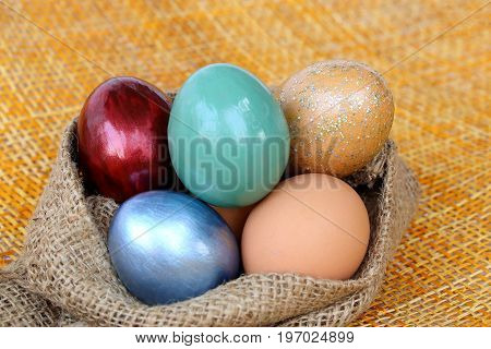 Colorful easter eggs in burlap hessian sacking bag.