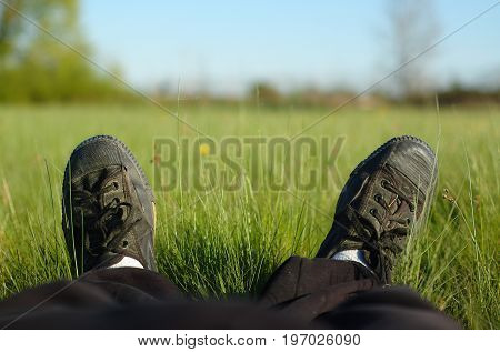 A person relaxing lengthened in a meadow on a sunny day.