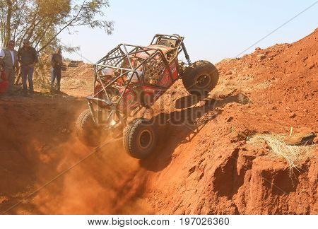 Red Car Ramping Out Of Steep Dugout, Three Wheels Suspended