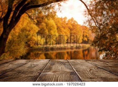 Autumn background close up of old empty wooden table over the lake with copy space