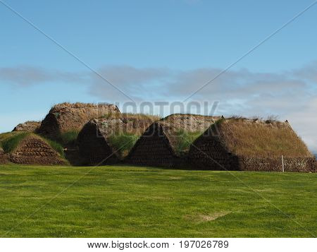 Glaumber - open-air folk museum - tradicional icelandic houses with turf roof and walls with green grass and blue sky