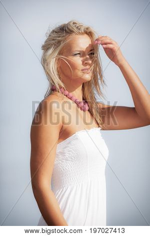 Clothing people concept. Cute woman in white dress. Attractive lady wearing red big necklace against sky