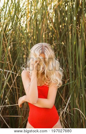 Beautiful blonde woman in a red piece-swimsuit posing in reeds