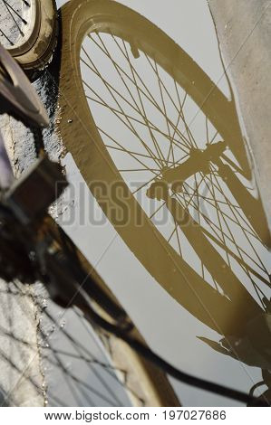 bicycle wheel reflection in water flood on street after raining