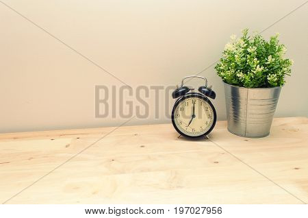 black vintage alarm clock times at 7 o'clock morning and green tree in silver pot small home decorative on wooden table and white wall vintage tone retro style