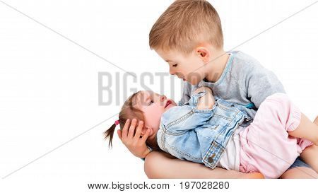 The brother looks into the eyes of his cute little sister, holding her in his arms, isolated on white background