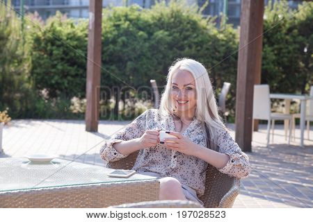 blonde girl sitting at the beach restaurant coffee drinkers