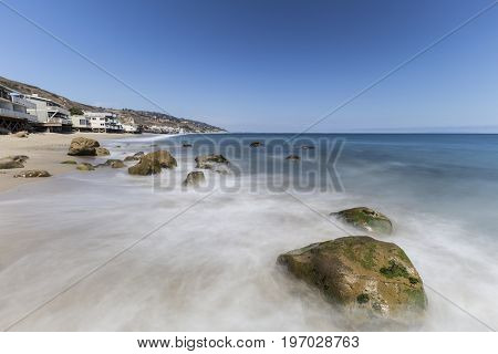 Oceanfront homes with motion blur waves at Carbon Beach in Malibu, California.