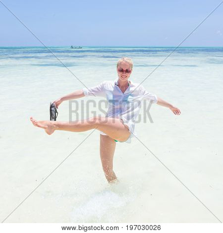 Young slim fit woman wearing white beach tunic making water splashes on white sandy beach. Vacation concept. Summer mood. Tropical beach setting. Paje, Zanzibar, Tanzania.