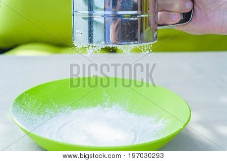 Close up male hand sifting powdered sugar in green plastic bowl