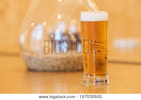 Dewy glass of beer standing on a wooden table