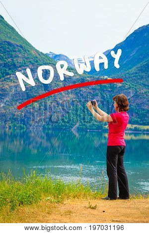 Tourism and travel. Woman tourist taking photo with camera enjoying mountains lake Oppstrynsvatnet view in Jostedalsbreen National Park Oppstryn (Stryn) Sogn og Fjordane county. Norway Scandinavia.
