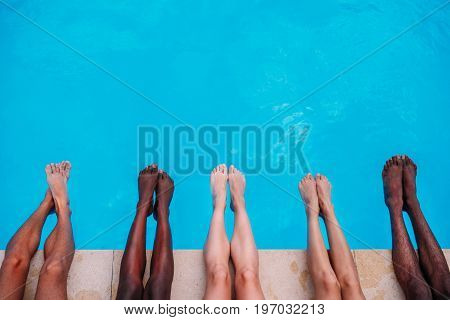Young People Lying Near Swimming Pool. Cropped Image Of Legs Over Blue Water