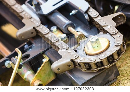 Agricultural harvesting industrial equipment concept. Agriculture machinery. Closeup of cutting chains