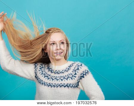 Hairstyles ideas happiness concept. Crazy teenage woman wearing winter jumper with windblown blonde hair