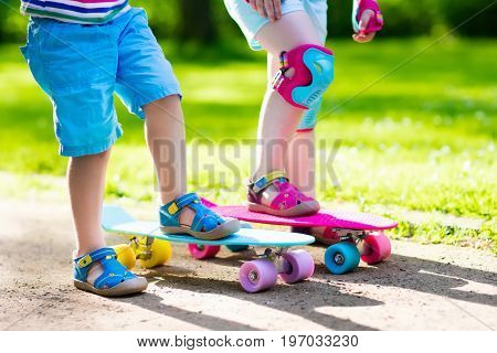 Children riding skateboard in summer park. Little girl and boy learn to ride skate board help and support each other. Active outdoor sport for kids. Child skateboarding. Preschooler kid skating.