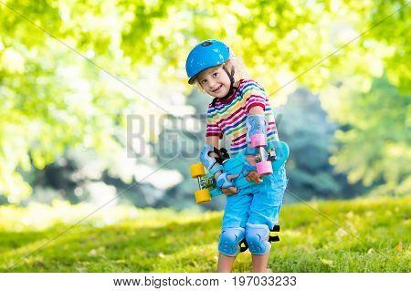 Child riding skateboard in summer park. Little boy learning to ride skate board. Active outdoor sport for school and kindergarten kids. Children skateboarding. Preschooler on longboard. Kid skating.